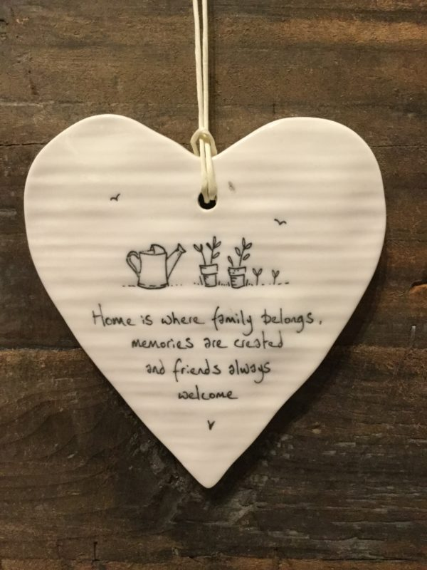 East Of India: White Porcelain Hanging Heart Sign with Black Writing. Saying: Family Home. Watering Can and Plants Image