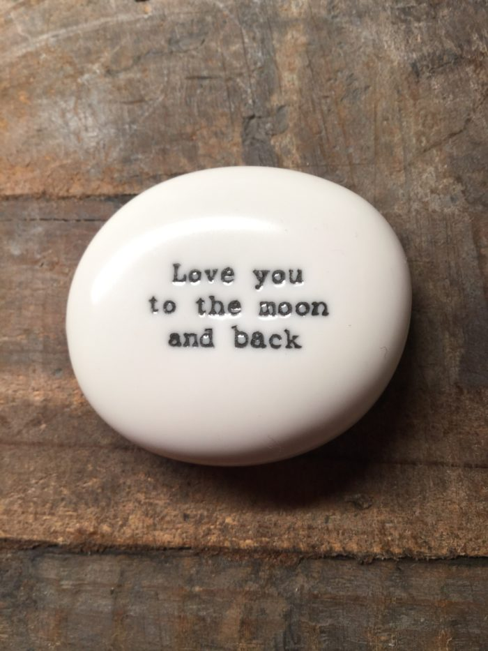 East Of India White Porcelain Pebble with Black Type Engraved. Saying: Love you To The Moon and Back.