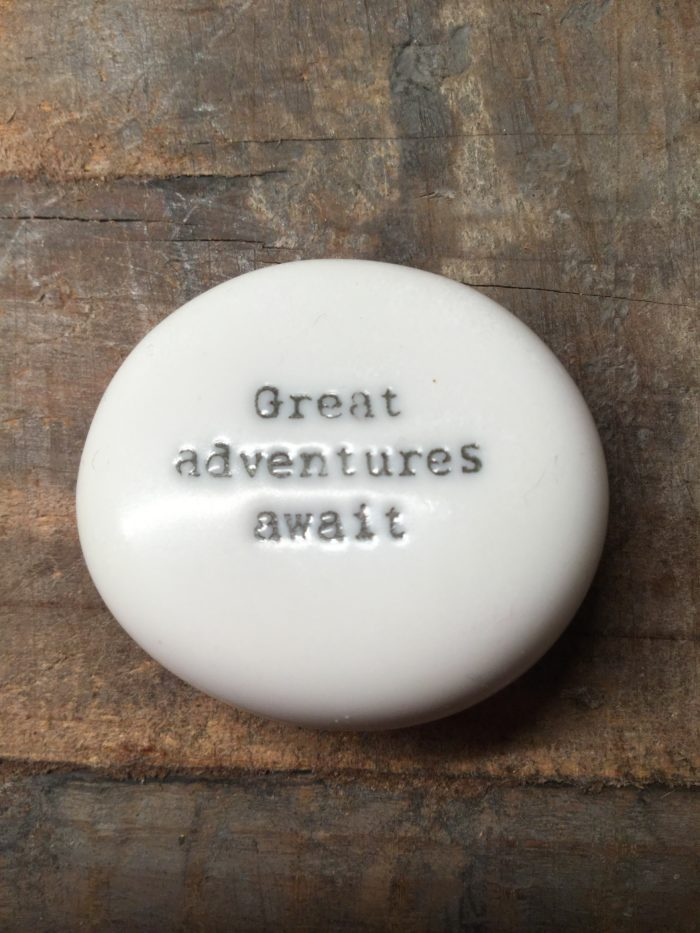 East Of India Small White Porcelain Pebble with Black Type Engraved. Saying: Great Adventure Awaits